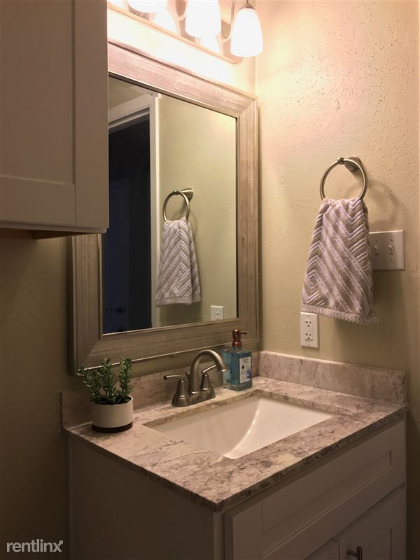 Designer lighting and framed mirror in bathroom