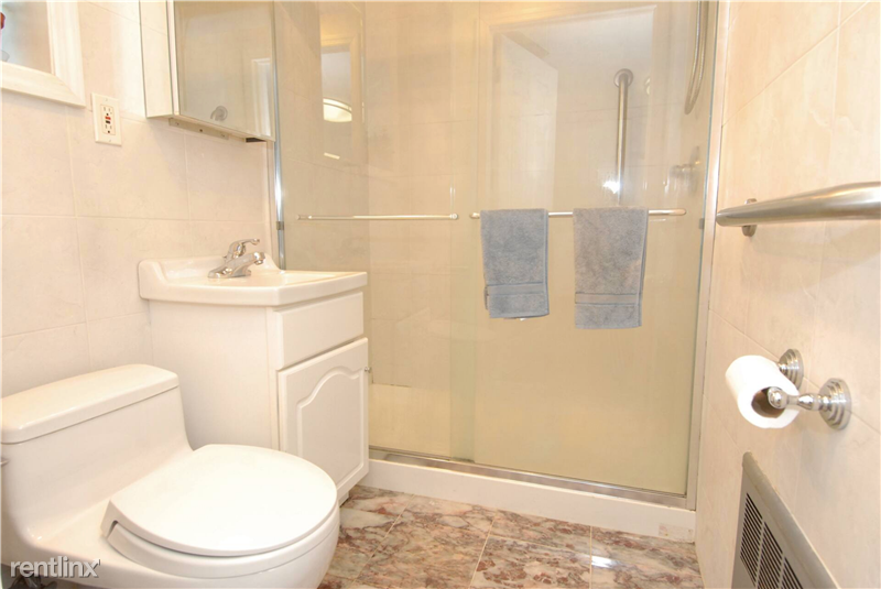 Modern bathroom w/ large walk-in shower and Toto toilet.