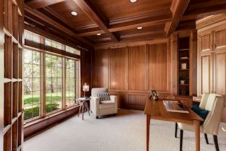 Paneled office with custom built-in work area and bookshelves, double french doors