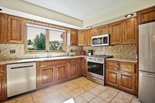 Kitchen features Granite counters & back splash, newer stainless appliances & great natural light!
