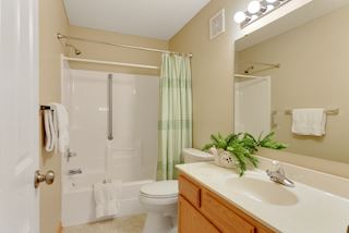 Main level full bath with large vanity & storage cabinet.