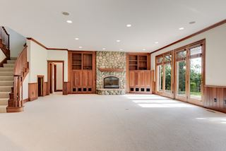 Built-in entertanment center, stone fireplace, doors to backyard