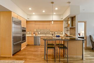 Kitchen has GE Monogram appliances, gas cooktop and island counter for eat in dining