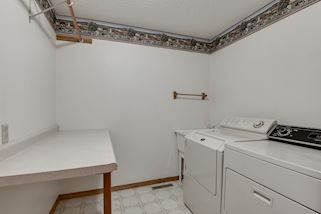 Main level laundry room with folding table and linen closet is a huge bonus!