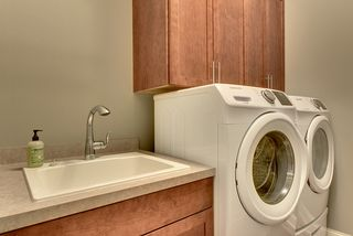 Laundry room has cabinets, sink and hanging bar