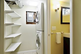 Lower level finished laundry space adjacent to bath with pocket door.