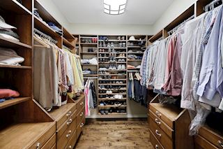 Master bedroom walk in closet with custom built ins