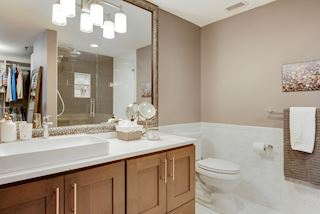 mirror in master bathroom reflects oversized walk in closet and designer shower with frameless glass doors