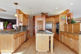 Eat in kitchen with plenty of cabinets, center island with granite countertops and a walk in pantry