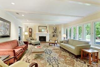 Gracious Living Room with fireplace and vast wall of windows to capture the view of  the tree lined canopy of the Kenwood Pkwy neighborhood