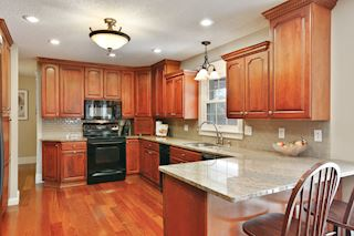 Kitchen has cherry cabinets, granite CT's and breakfast bar.