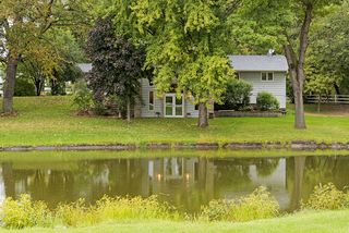 High canopy of trees, rolling acreage and huge pond provide tranquil setting.