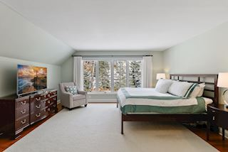 Master bedroom with large windows overlooking back yard