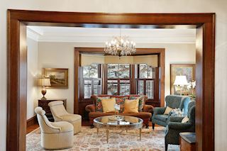 Inviting living room with detailed mouldings and two bay windows.