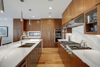 Walnut cabinetry, quartz counters and backsplash