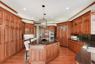 Large center island, cooktop (gas hook-up), desk area, and extensive cabinetry
