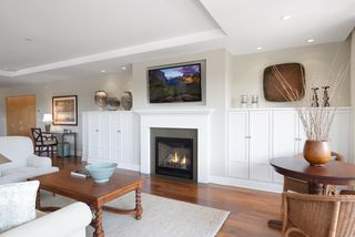 Beautiful gas fireplace with mounted TV above and flanked by custom built-ins