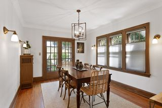 Dining room with refinished hardwood floors, abundant light, new lighting and french doors.