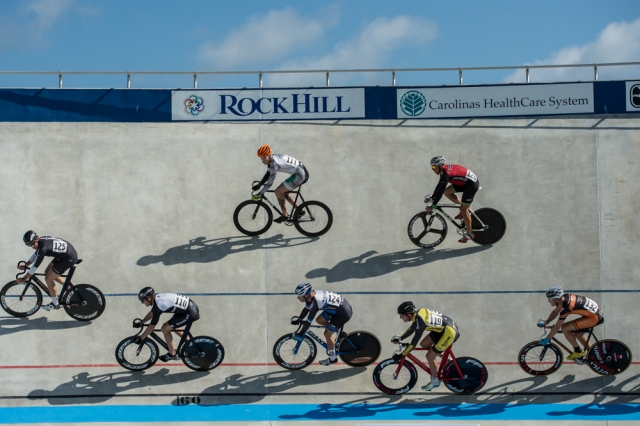 Riders circle the track during the men's scratch race heats