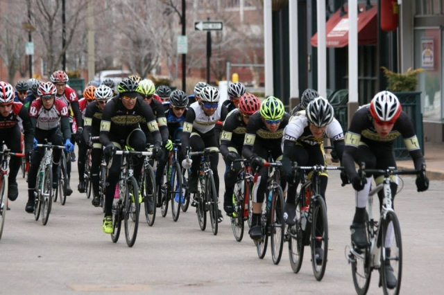 The Men's A field takes to the front stretch of the Main Street Criterium at Lindenwood.
