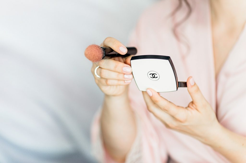 girl putting on chanel powder