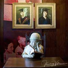 Sculpture of a child reading a book below graduation portraits of Mariano and Josefa, parents of former Philippine president, Ferdinand Marcos,