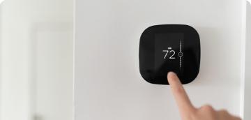 Homeowner adjusting their smart thermostat enrolled in the Peak Time Savings program