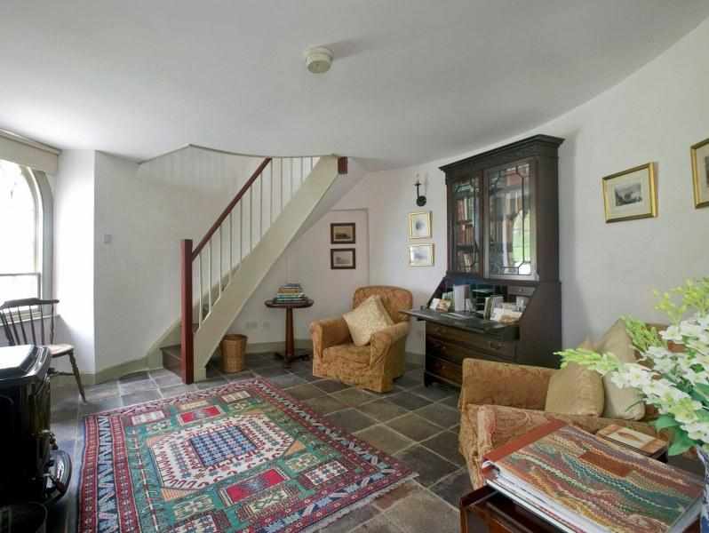 The gorgeous sitting room is set in the Turret end of the cottage and has a lovely wood-burner and flagstone flooring underfoot.
