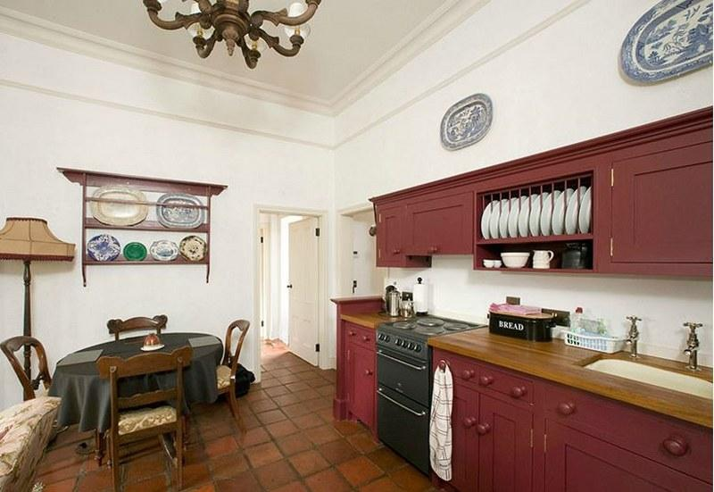 The charming kitchen with its striking red units and tiled floor.