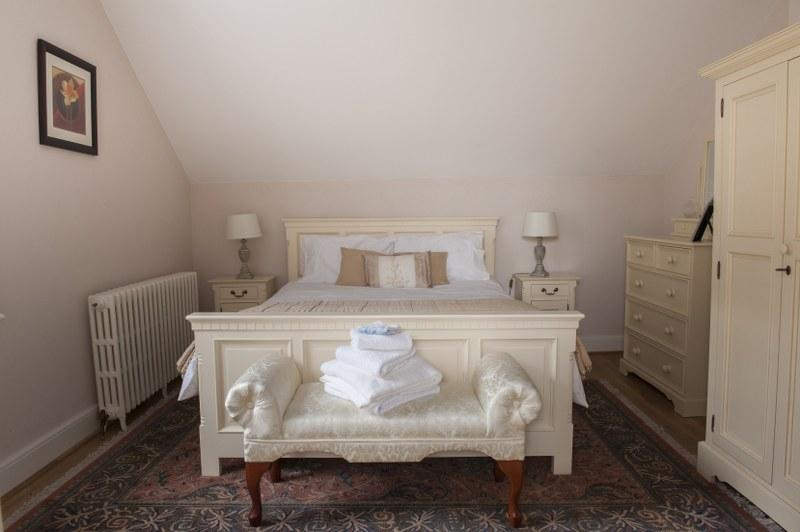 The gorgeous double bedroom in The Brooke with its luxury bed linen and country cottage look.
