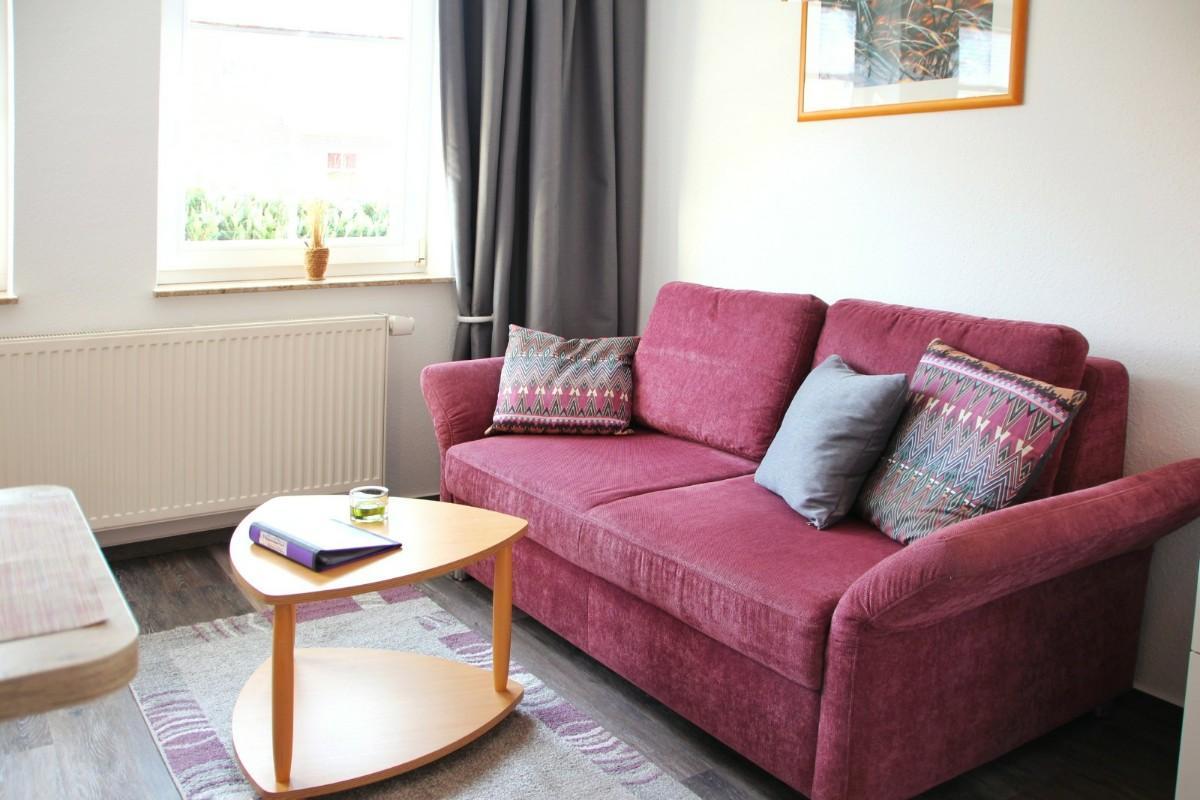 Der warme Brombeerton der Couch findet sich in vielen Details der Wohnung wieder.