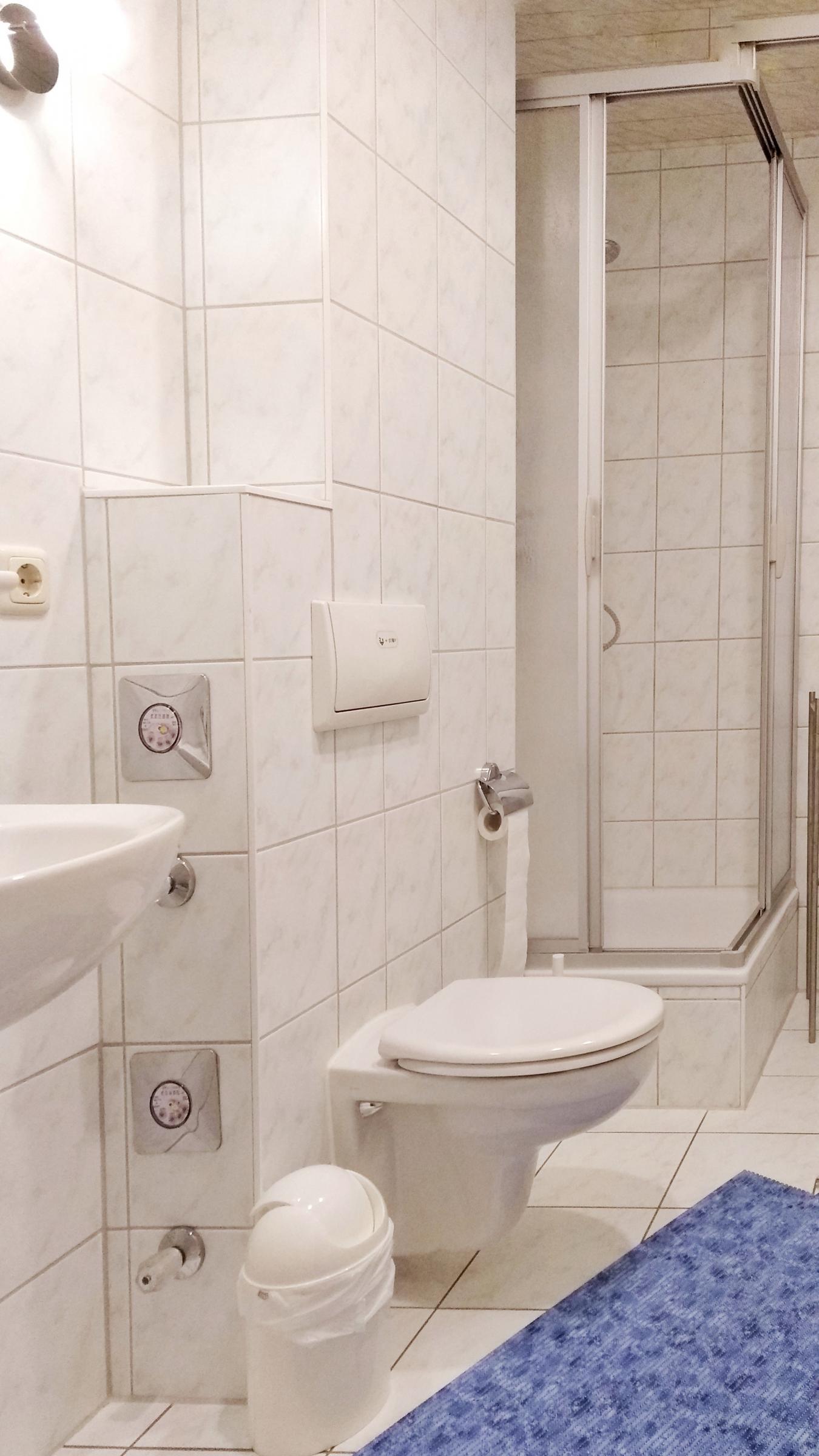 Dusche / WC in hellen Fliesen und hellem LED-Licht.