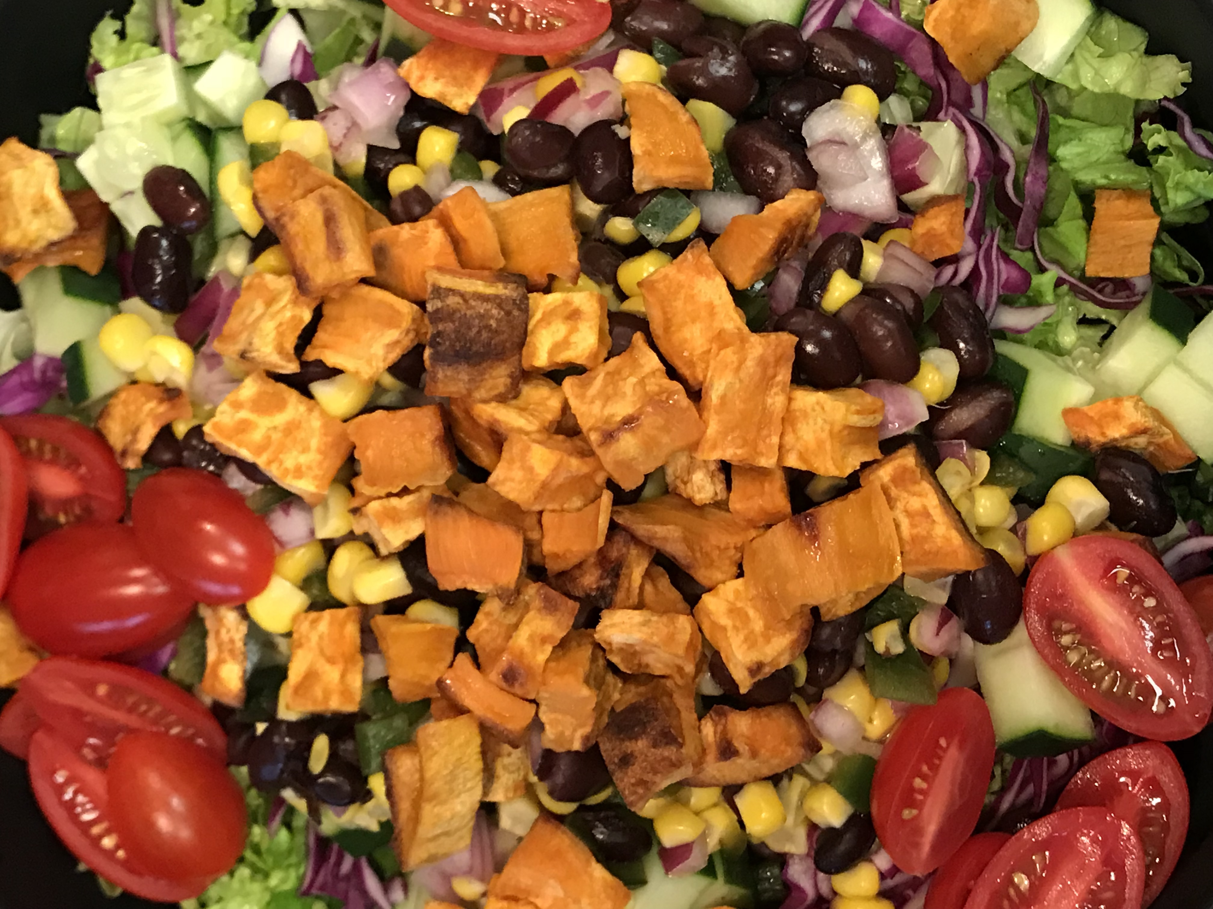 Roasted sweet potatoes with corn salsa, black beans, red cabbage, kale, grape tomatoes, cucumbers, and a light housemade vinaigrette. Get filled with all of the good stuff!