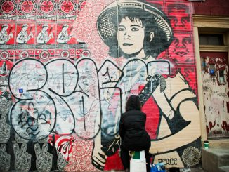 Lauren Cassady removes graffiti from the Shepard Fairey mural at Frankford Avenue and Norris Street in Philadelphia.