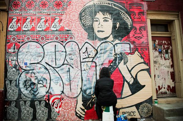 Lauren Cassady removes graffiti from the Shepard Fairey mural at Frankford Avenue and Norris Street in Philadelphia.
