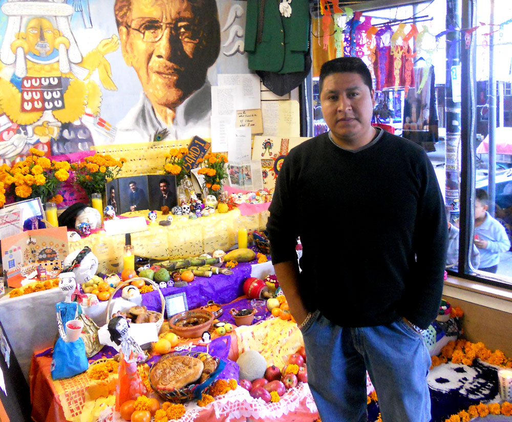 "Jair Andrade stood in front of the ""ofrenda"" at the shop he owns."