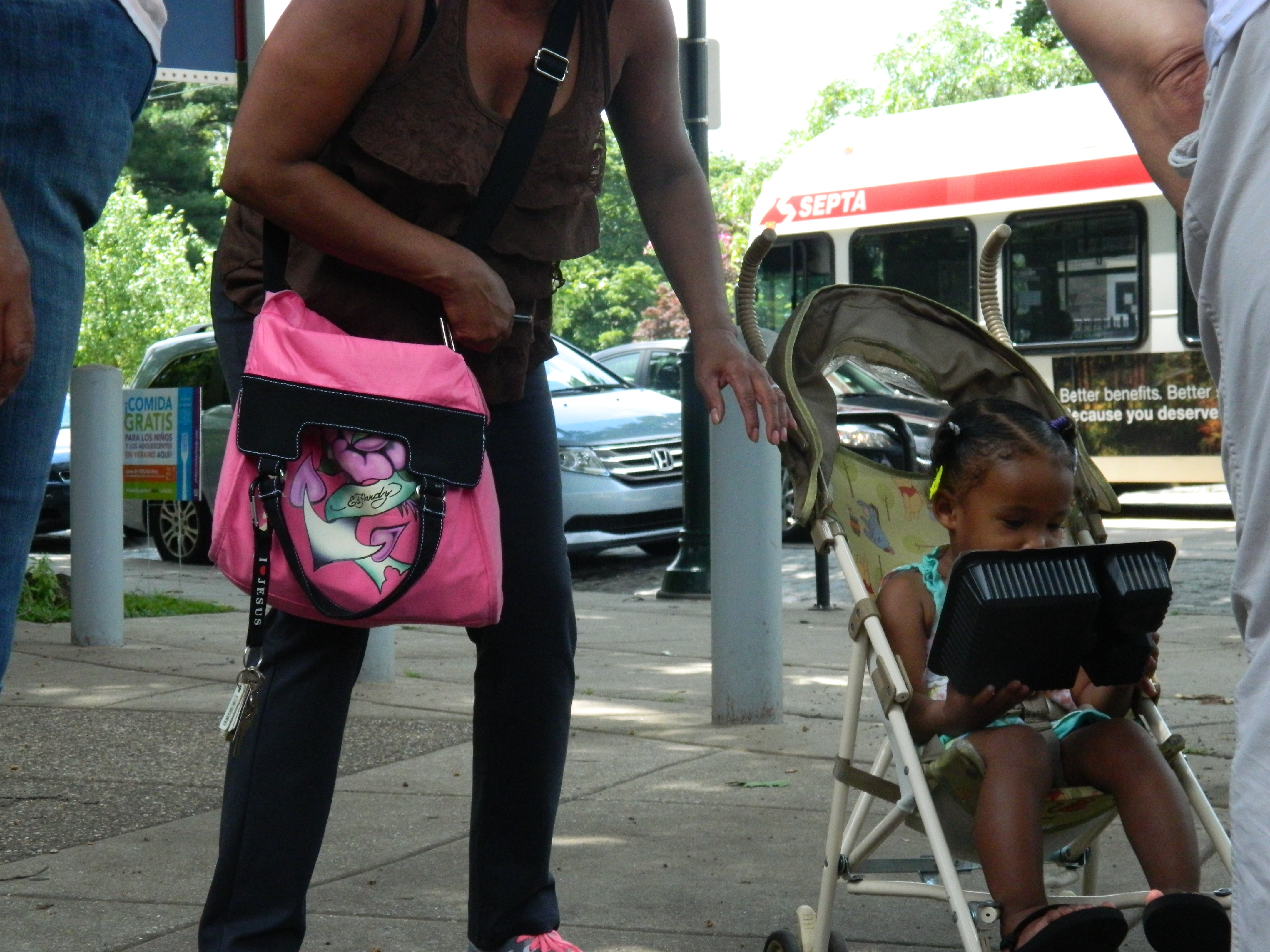 A young girl stops outside Lovett Memorial Library with her mother to enjoy a free lunch