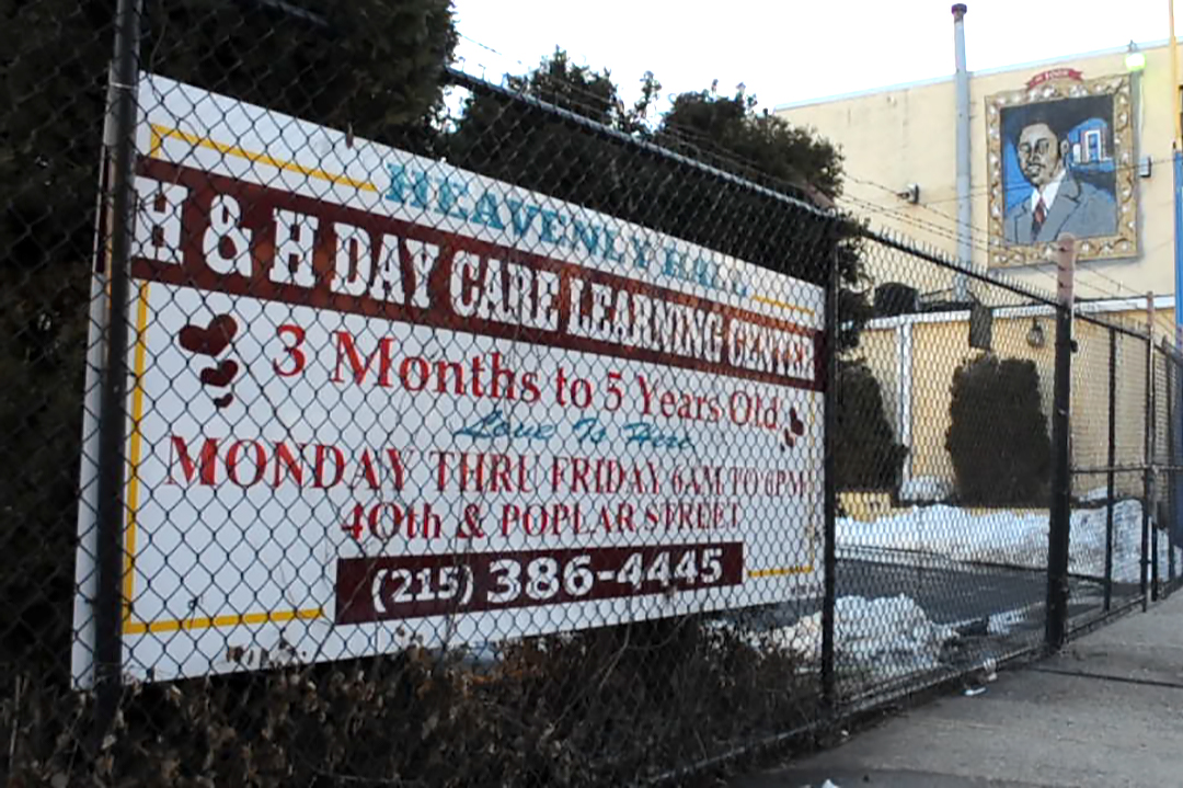 A sign on a fence outside a daycare center.