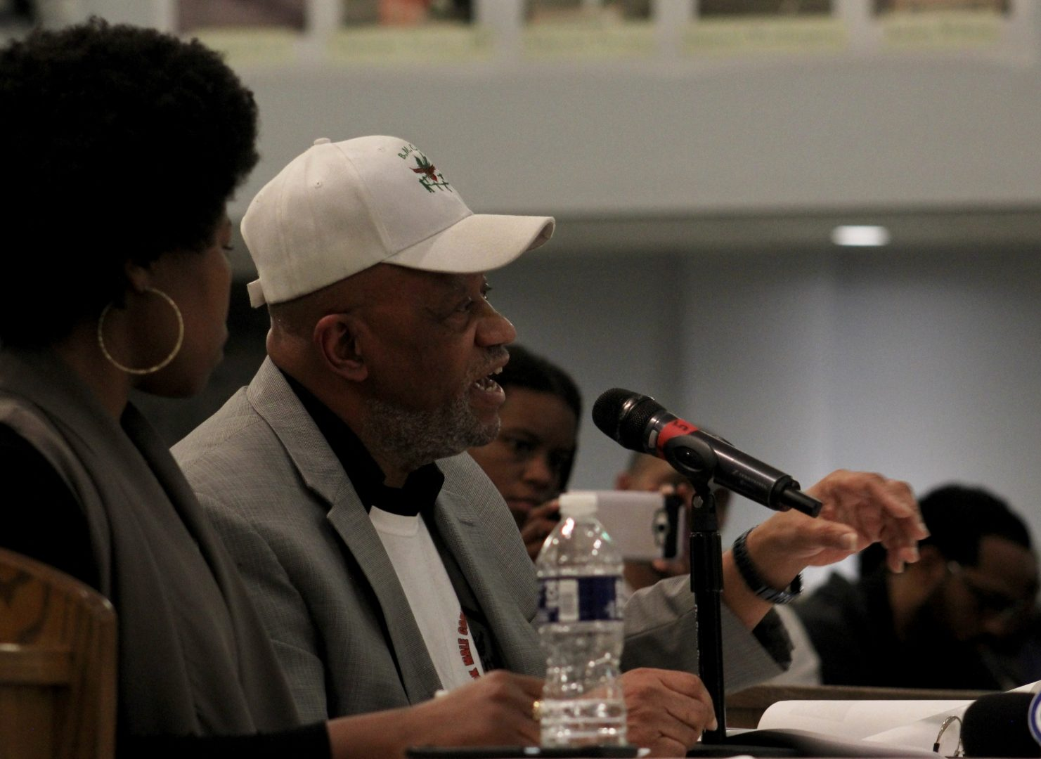 Stanley Crawford sits at the table near the front of the church and speaks into a microphone. He is wearing a hat with the logo of the Black Male Community Council.