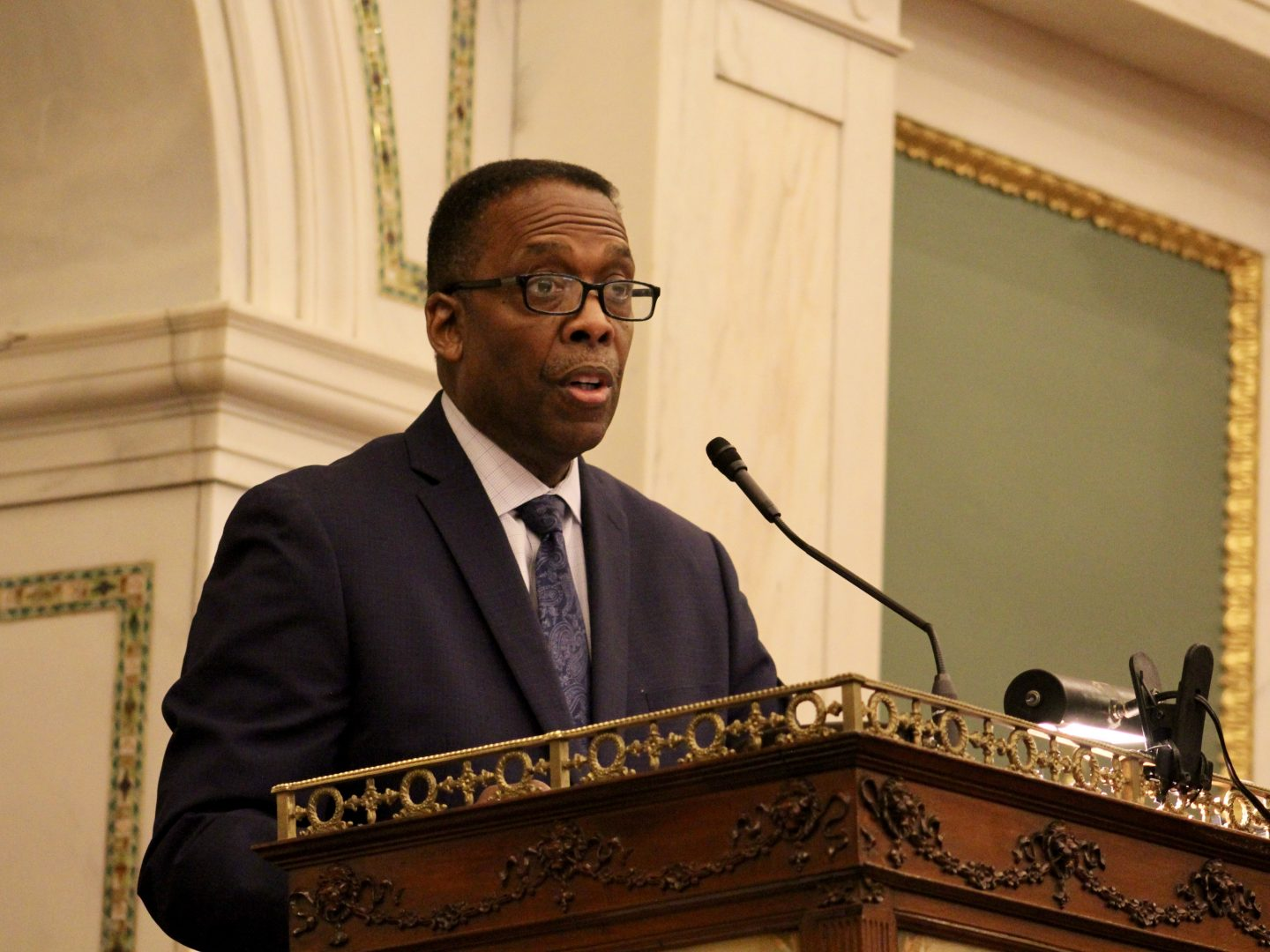 Council President Darrell Clarke stands and speaks into a microphone.