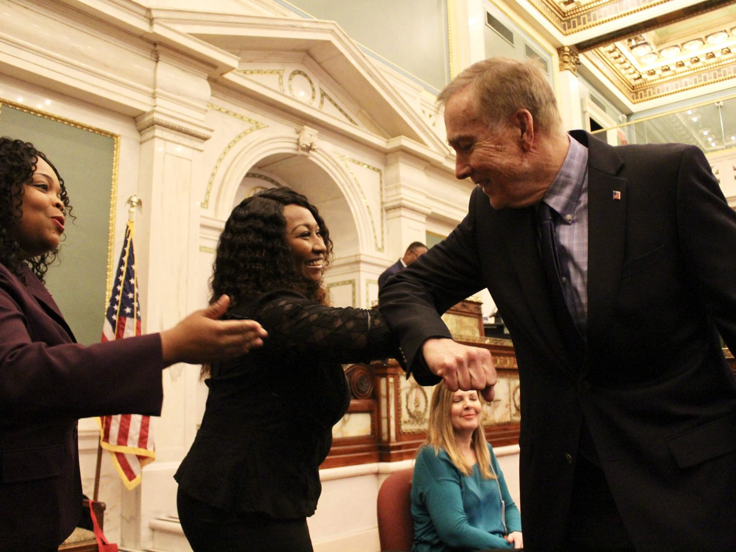 Councilmember Brian O'Neill greeted Minister Reshaun Carlton with an elbow bump.