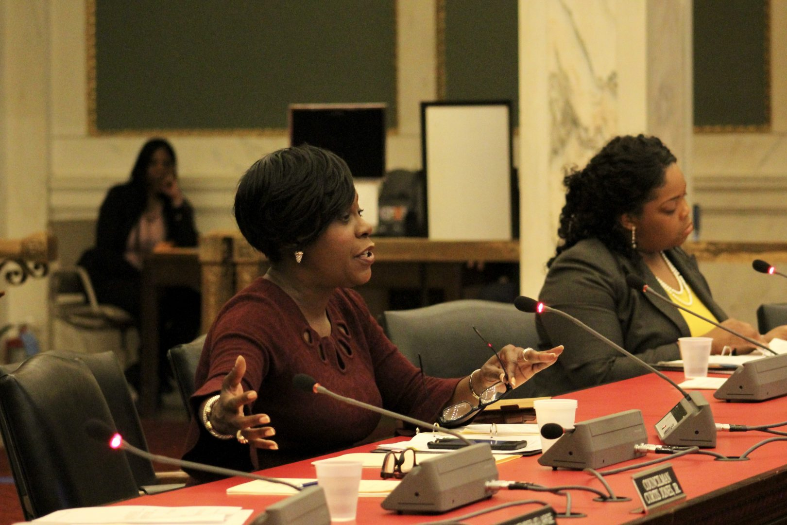 Majority Leader Cherelle Parker gestures with both hands while sitting at a table in the City Council chamber and speaking into a microphone.