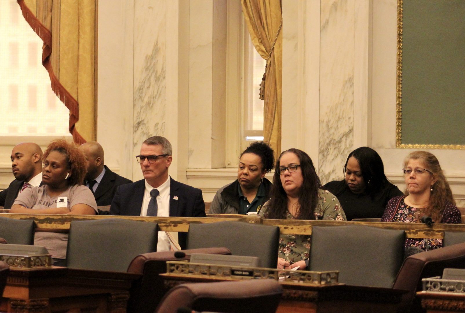 Dispatchers and other individuals sit in the audience section of the City Council chamber and observe police and fire officers testify at a hearing on March 11.
