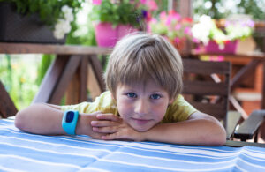 Cute boy with blue smart watch lying on the table at terrace