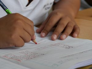 boy writing on paper with pencil in classroom