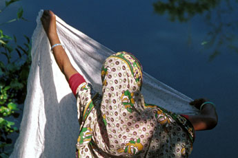 A woman folds a sari in Matlab, Bangladesh