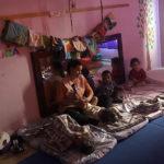 professora faz massagem indiana em uma criança, enquanto uma criança dorme ao lado esquerdo e duas crianças prestam atenção ao lado direito
