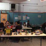 Vista do laboratório de informática com uma mesa ao centro onde estão dispostos os projetos dos alunos
