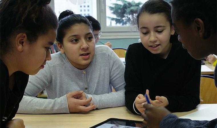 Crianças reunidas ao redor de uma mesa discutem conteúdo visto no tablet