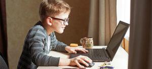 Criança com óculos mexendo em computador